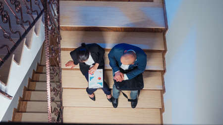Top view of businesspeople doing overtime late night tired on deadline working sitting on stairs analysing graphs from clipboard. Company manager overworking at corporate job explaining project.