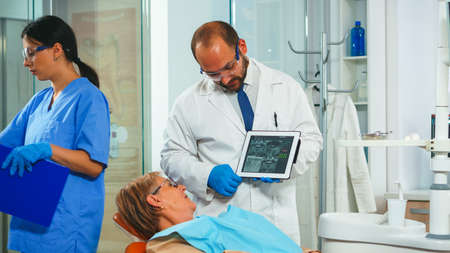 Orthodontist using tablet explaining dental x ray to patient sitting on dental chair in stomatologic office. Dentist showing to old woman radiography using digital device working in modern clinic. Standard-Bild