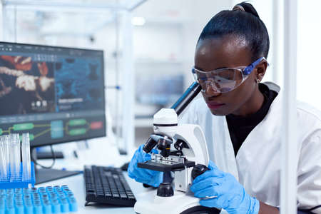 Medical researcher with african ethnicity using microscope doing investigation and evaluates sample. Black healthcare scientist in biochemistry laboratory wearing sterile equipment.