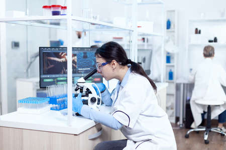 Expert in genetics doing research using microscope to analise chemical from human adn. Chemist wearing lab coat using modern technology during scientific experiment in sterile environment.