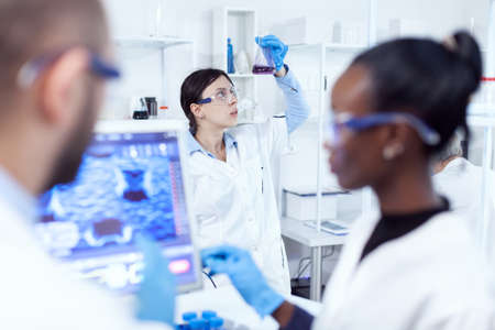 Chemistry exppert looking at scientific sample in busy laboratory. Multiethnic team of medical researchers working together in sterile lab wearing protection glasses and gloves.