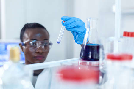 African scientist staring at sample blue liquid in test tube chemical. Black researcher in sterile laboratory conducting pharmacology experiment wearing coat.