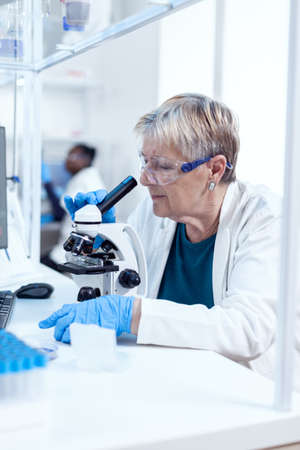 Senior scientist woman with protection glasses doing genetic investigation using microscope with african assistant in the background.. Elderly researcher carrying out scientific research in a sterile lab using a modern technology.
