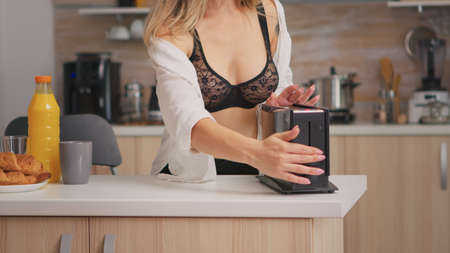 Sexy beatiful woman making roasted bread using toaster wearing black lingerie. Young attractive seductive lady in the morning in cozy interior home preparating delicious and healthy breakfast.
