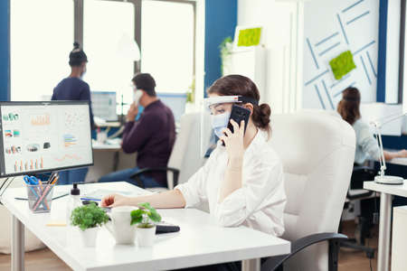 Business woman in office wearing face mask against covid 19 having a conversation on smartphone. Multiethnic coworkers working respecting social distance in financial company.