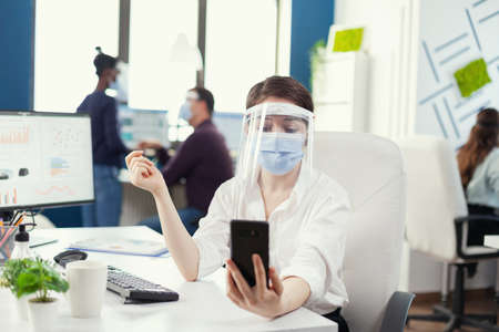 Businesswoman having a corporate video conference using smartphone wearing face mask. Colleagues working respecting social distance during global pandemic with coronavirus.