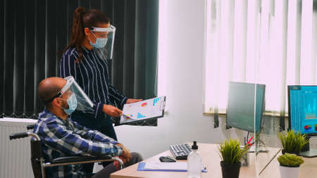 Business people wearing protective mask in new normal office discussing strategy, businessman sitting in wheelchair. Team working in profesional workspace in corporate company during covid-19 pandemic