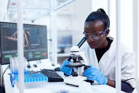 African doctor in pharmacology looking for sign of patoloy in patient sample using microscope. Black healthcare scientist in biochemistry laboratory wearing sterile equipment. Banque d'images