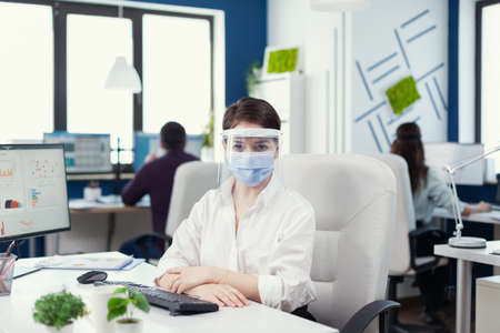 Entreneur wearing face mask and vizor looking at camera during covid19. Business team working in financial company respecting social distance during global pandemic.