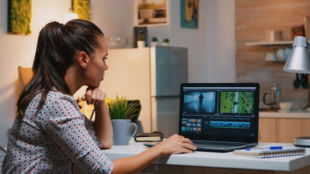 Videographer editing from home on professional laptop sitting on desk in modern kitchen in midnight. Creative video editor working at night at new project processing audio film montage.