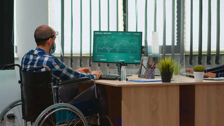 Disabled businessman sitting in wheelchair with protection mask cleaning hands before checking financial data in business modern office. Handicapped freelancer with visor respecting social distance Reklamní fotografie