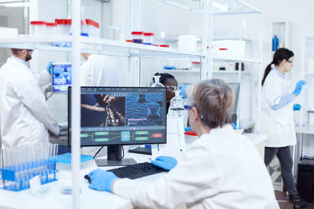 Senior scientist in pharmaceuticals laboratory doing genetic research wearing lab coat with team in the background. African assistant engineering adn.