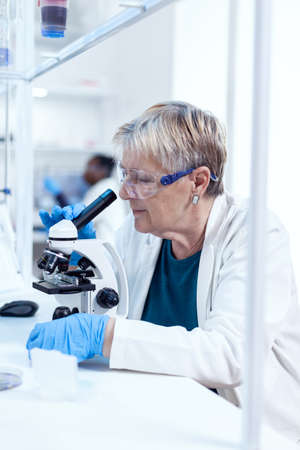 Concentrated senior scientist conducting genetic experiment using microscope. Elderly researcher carrying out scientific research in a sterile lab using a modern technology.
