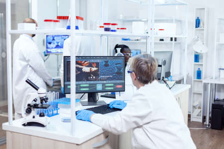 Elderly researcher engineering human adn using softtware on powerfull computer. Senior scientist in pharmaceuticals laboratory doing genetic research wearing lab coat with team in the background.