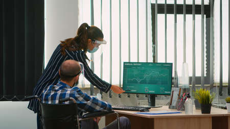 Woman pointing on desktop talking with disabled colleague in new normal office in front of computer. Team of financial expert working on computer analysing economic graphs respecting social distance.