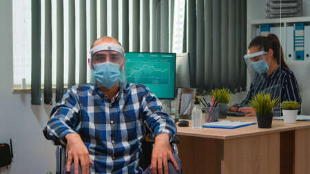 Handicapped businessman in wheelchair with mask having online conference in business office during covid-19 pandemic. Immobilized freelancer working in financial company respecting social distance. Фото со стока