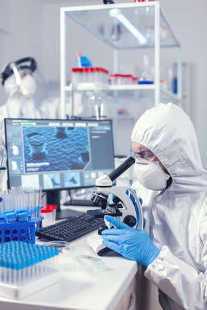 Medic and nurse dressed in ppe equipment checking evolution of coronavirus in laboratory. Scientist in protective suit sitting at workplace using modern medical technology during global epidemic. Standard-Bild