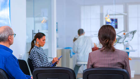 Back view of woman filling in dental form sitting on chiar in waiting room preparing for dental implants while doctor exemination patient in background. Crowded professional orthodontist office.