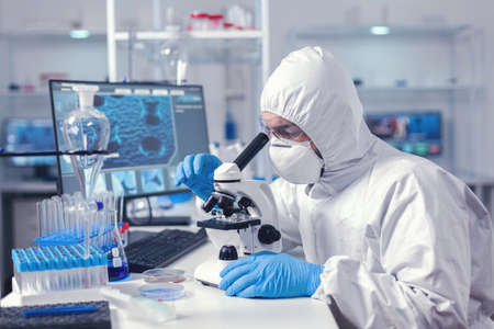 Biochemist testing sample for virus using microscope dressed in ppe suit. Virolog in coverall during virus outbreak conducting healthcare scientific analysis.