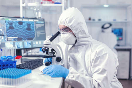 Doctor researching and evaluating virus using microscope in laboratory wearing ppe. Scientist in protective suit sitting at workplace using modern medical technology during global epidemic.
