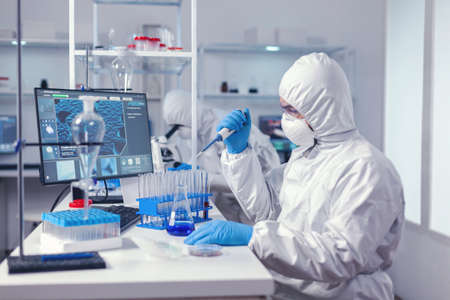 Healthcare scientist taking sample from test tube using automatic pipette in modern lab. Chemist in modern laboratory doing research using dispenser during global epidemic Standard-Bild
