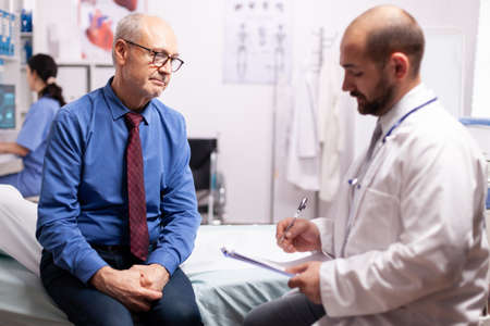 Surgeon wearing stethoscope discussing treatment in examination room with senior man. Elderly patient having a converstation with medical stuff in private clinic during consultation.