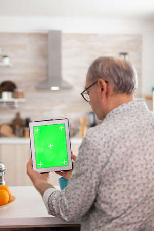 Over the scholder shot of grandfather using tablet pc with green screen in kitchen while enjoying his breakfast. Elderly person with chroma key isolated mock-up mockup for easy replacement
