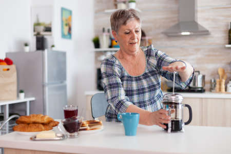 Old woman pushing down the lid of french press while making coffee for breakfast in kitchen. Elderly person in the morning enjoying fresh brown cafe espresso caffeine from mug filter relax refreshment