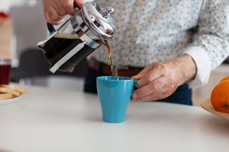 Close up of elderly man enjoying a hot drink after pouring coffee in cup during breakfast sitting in modern kitchen. Elderly person in the morning drinking fresh brown espresso from vintage mug 写真素材