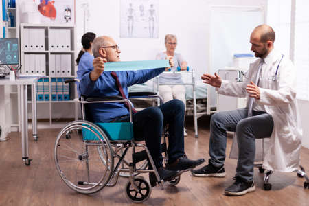 Disabled senior man doing his exercises in hospital with doctor. Elderly invalid patients in hospital following rehabilitation treatment with help from medical personal.