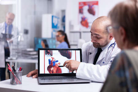 Physician using laptop showing heart disease to elderly woman pointing on laptop sitting in hospital room talking with senior patient. Team of doctors working in background using clipboard and x-ray