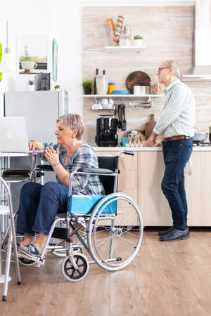 Disabled senior woman in wheelchair working from home at laptop in kitchen and husband preparing breakfast. Handicapped businesswoman, disabilty entrepreneur paralysis for elderly retired woman
