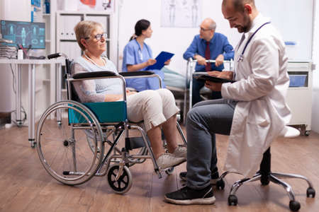 Medical physician discussing with handicapped senior woman sitting in wheelchair. Man with disabilities ,walking frame sitting in hospital bed. Health care system, clinic patients.