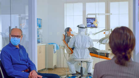 People with protection masks discussing in reception area waiting doctor in dental clinic while stomatologist working in background wearing ppe suit. Concept of new normal dentist visit
