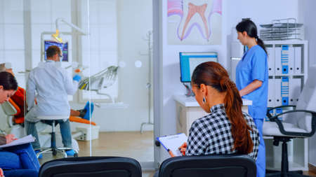 Back view of woman filling in dental document sitting on chiar in waiting room preparing for teeth exemination while doctor working in background. Concept of crowded professional orthodontist office.