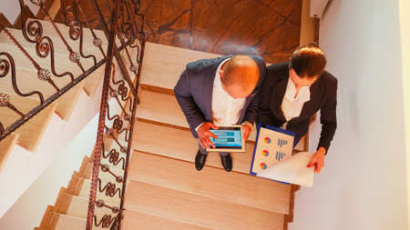 Top view of coworkes reading annual reports using tablet and documents standing on staircase of business building. Group of professional successful businesspeople working in modern financial workplace