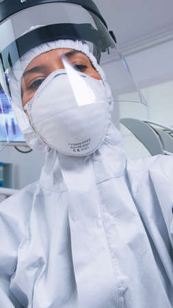 Patient pov of dentist holding dental tools wearing covid protection suit treating patient in new normal clinic. Stomatolog wearing safety gear against coronavirus during heatlhcare check of person.