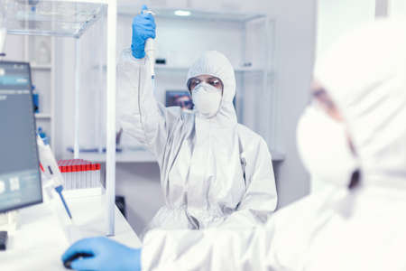 Lab scientist in healthcare lab holding micropipette with sample dressed in ppe suit against coronavirus. Team of microbiologists in research laboratory conducting experiment during global pandemic with covid19. 写真素材