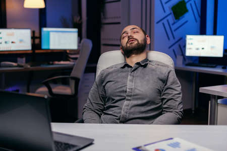Overworked exhausted man sleeps on chair in empty office. Workaholic employee falling asleep because of while working late at night alone in the office for important company project.