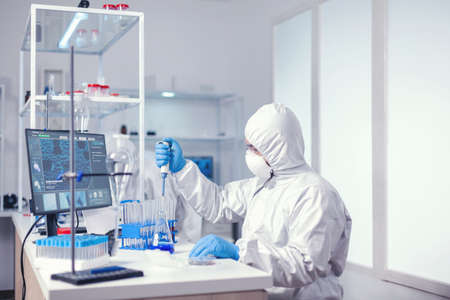 Biochemistry scientist taking sample of blue solution with pipette to develop vaccine. C
