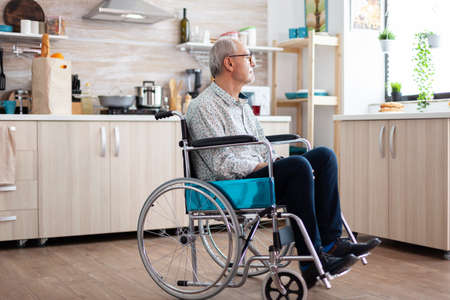 Lonely invalid man sitting in wheelchair looking through kitchen window. Elderly handicapped pensioner after injury and rehab, paralysis and disability for depressed invalid full of sorrow.