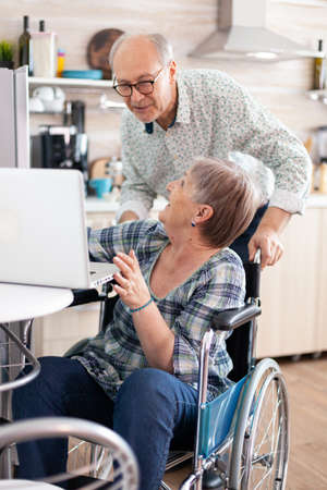 Happy disabled senior woman in wheelchair and husband saying hello during video call on laptop in kitchen talking and laughing . paralyzedperson using modern communication online internet web tech Imagens