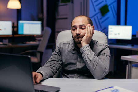 Bored sleepy businessman working on laptop doing overtime at workplace. Workaholic employee falling asleep because of working late at night alone in the office for important company project.