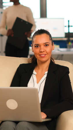 Hispanic business woman smiling at camera sitting on couch typing on computer while diverse colleagues working in background. Multiethnic coworkers analysing startup financial reports in modern office