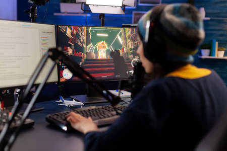Pro gamer sitting on gaming chair at desk and talking into microphone for space shooter video games competition. Woman streaming online videogames for esport tournament in room with neon lights