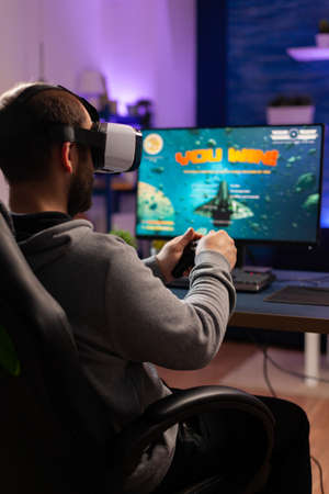 Gamer losing online space shooter tournament game wearing virtual reality headset. Esport man siting on gaming chiar late at night in home studio using professional equipment