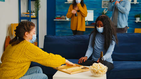 Multiethnical women playing backgammon wearing face mask as prevention for covid 19 spread during global pandemic sitting on sofa drinking beer and eating popcorn. Enjoying board games in outbreak
