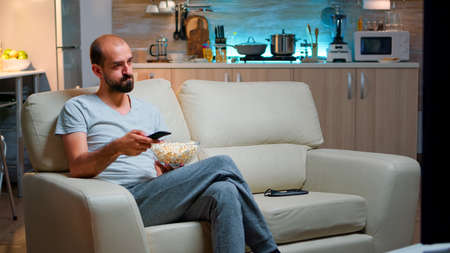 Bored man switching TV channels, holding popcorn in hads late at night while trying to watch entertainment television. Using remote control to choose favourite station and enjoy quality time Foto de archivo