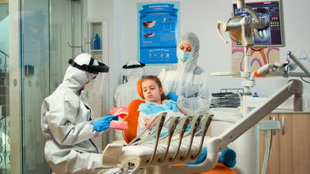 Stomatologist in ppe suit holding plaster model of the mandible speaking with girl patient. Medical team wearing face shield coverall, mask, gloves, showing correct dental hygiene using teeth skeleton Stock Photo