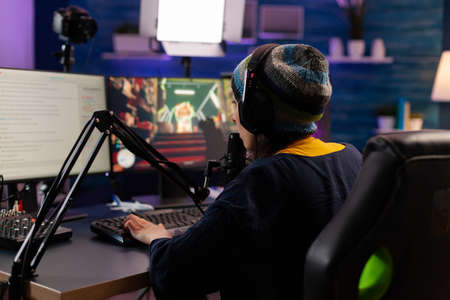 Professional streamer playing shooter games wearing headphones and talking into microphone via streaming chat. Gamer making online videogames with new graphics on powerful computer
